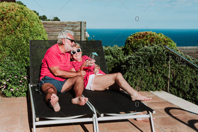 High angle of relaxed senior couple lying on loungers on terrace and drinking refreshing tropical cocktails while enjoying summer holiday