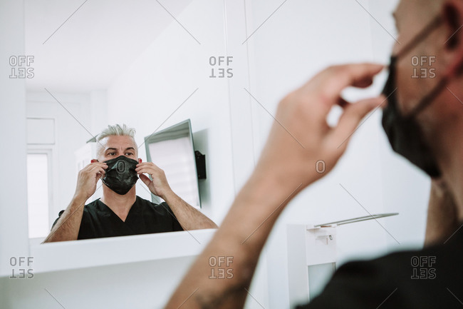 Serious male tattoo artist standing in salon in front of mirror and putting on protective mask before procedure