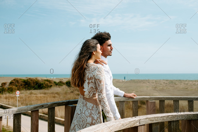 Side view of relaxed young couple in stylish white outfits standing on wooden bridge and admiring landscape while spending romantic holidays at seaside