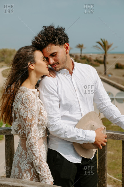 Side view of relaxed young couple in stylish white outfits standing on wooden bridge with eyes closed cuddling each other while spending romantic holidays at seaside