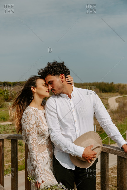 Loving young woman in stylish wedding dress with bouquet embracing gently handsome groom during romantic journey in nature