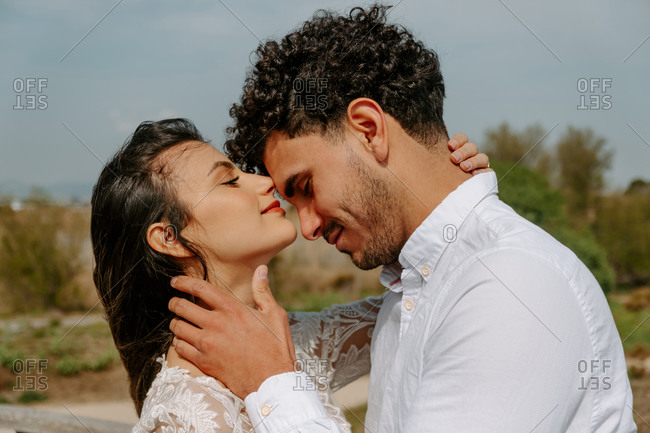 Young curly haired groom and charming bride in elegant white dress cuddling and enjoying each other with eyes closed during wedding session on seashore