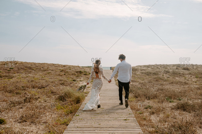 Full body back view of unrecognizable young newlywed couple in stylish clothes with bouquet holding hands and walking on wooden pathway towards sea
