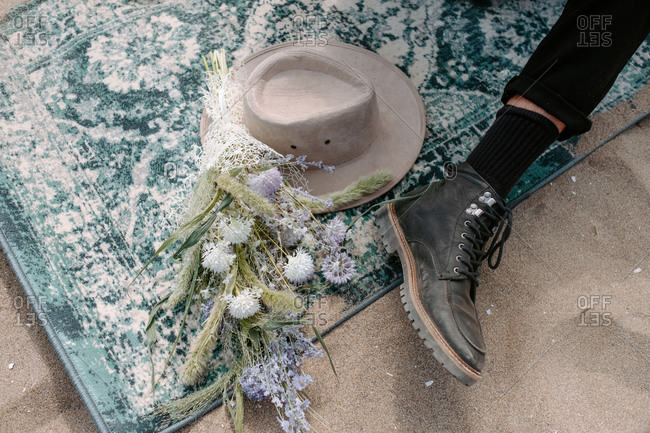 From above of crop anonymous groom in black boots sitting on vintage rag near wedding bouquet and stylish bohemian feminine hat