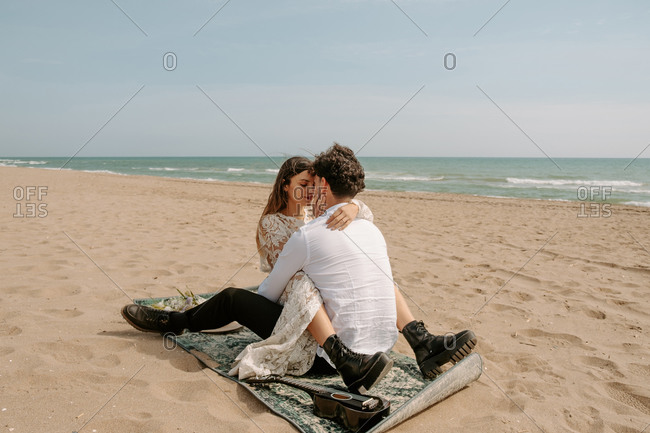Full length romantic newlywed young couple in stylish clothes hugging and kissing while sitting with ukulele on sandy beach