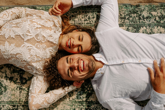 From above romantic newlywed young couple in stylish clothes lying opposite with face to face with eyes closed cuddling on vintage rug on sandy beach