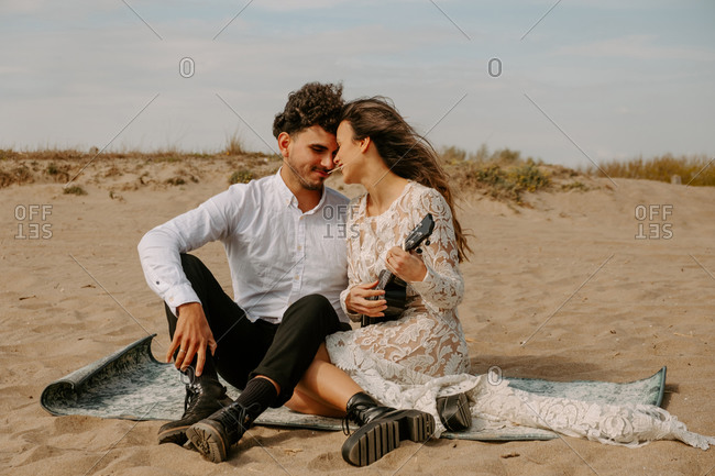Full length happy young newly married couple in bohemian elegant clothing playing ukulele guitar while sitting together on sandy beach