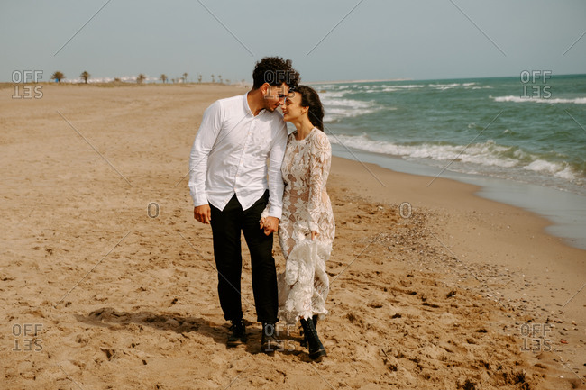 Full length happy young bride and groom in elegant boho outfits holding hands and embracing each other with eyes closed while strolling along sandy beach with waving sea
