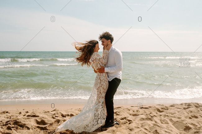 Full body side view of cheerful young bride and groom in stylish wedding costumes standing embracing each other on sandy beach near waving sea and enjoying each other