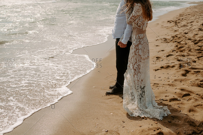 Side view of crop unrecognizable groom and bride in beautiful wedding clothes standing on sand near waving sea during romantic journey