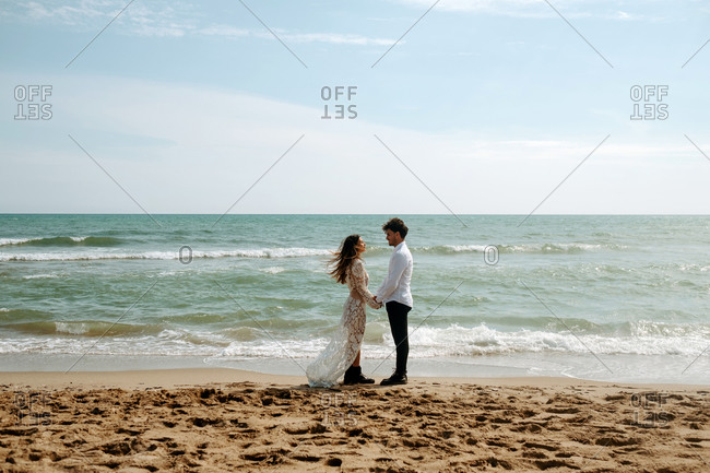 Side view of groom and bride in beautiful wedding clothes standing on sand near waving sea during romantic journey holding hands and looking at each other smiling
