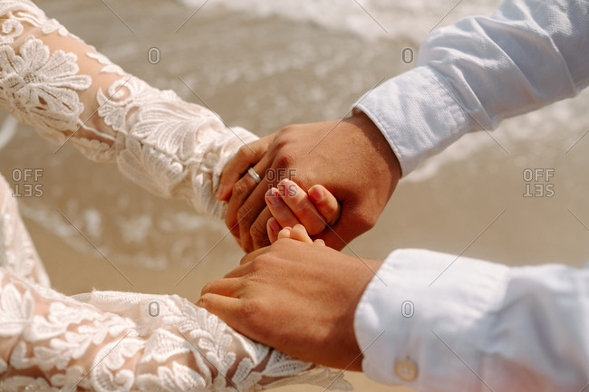 Side view of crop anonymous newly married couple in elegant white wedding clothes holding hands while standing against waving sea