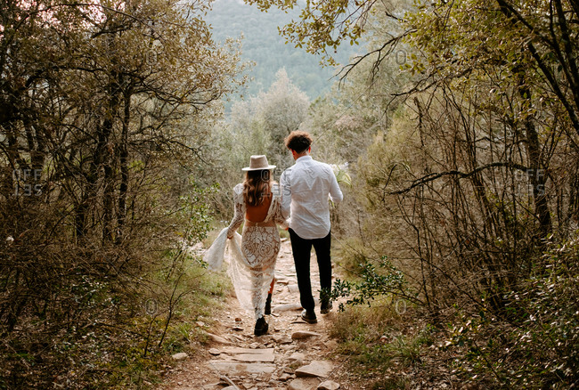 Back view of unrecognizable young bride and groom in stylish wedding outfits walking together on narrow stony path in mountainous forest in Morro de Labella in Spain