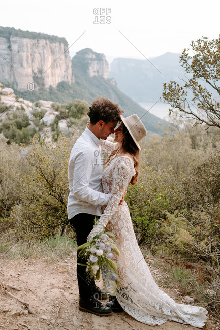 Full body side view of romantic young newly married couple in wedding outfits with bouquet embracing and kissing while standing against picturesque mountain landscape of Morro de Labella in Spain