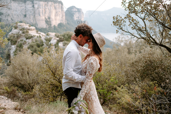 Side view of romantic young newly married couple in wedding outfits with bouquet embracing and kissing while standing against picturesque mountain landscape of Morro de Labella in Spain