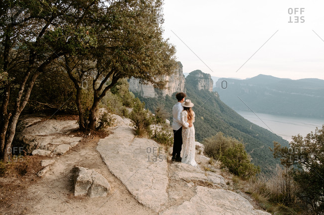 Back view of full length of unrecognizable romantic young newlywed couple in elegant costumes with wedding bouquet embracing each other while standing on edge of rocky cliff of Morro de Labella in Spain contemplating the views