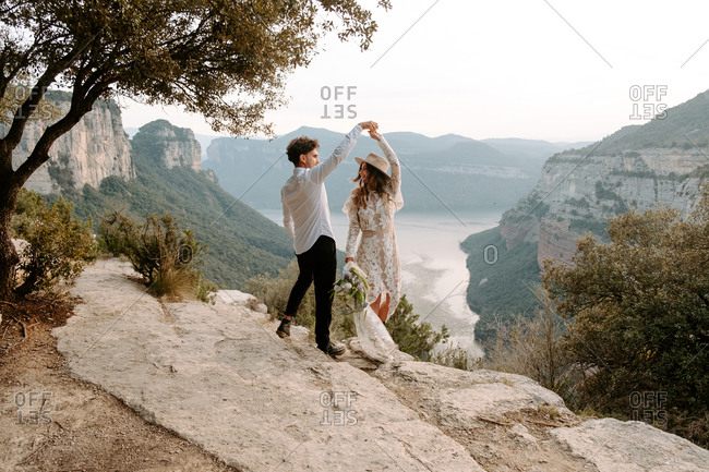Full length of romantic young newlywed couple in elegant costumes with wedding bouquet dancing on edge of rocky cliff of Morro de Labella in Spain