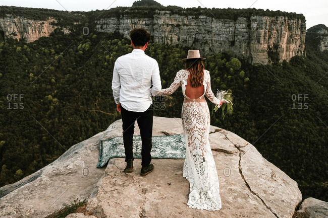 Full body back view of unrecognizable newlywed couple in elegant trendy wedding clothes with bouquet standing on edge of rocky cliff while visiting Morro de Labella in Spain