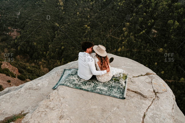 From above back view of newlywed young man and woman in elegant clothes sitting on top of rocky cliff of Morro de Labella and kissing gently