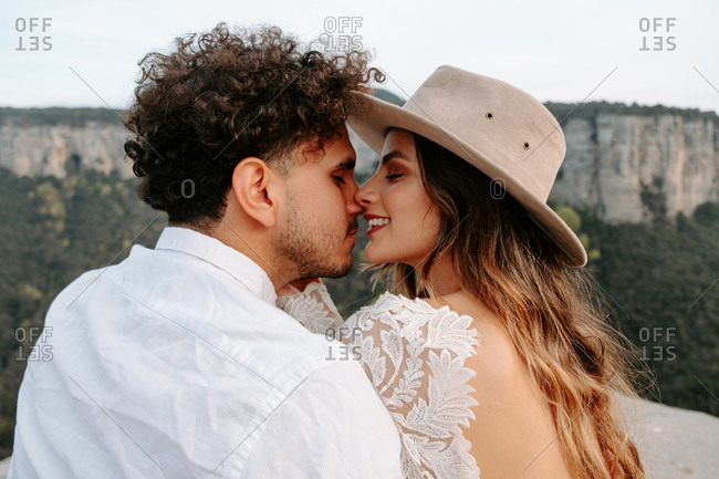 Back view of happy young couple in stylish wedding outfits kissing tenderly while enjoying romantic moments together against blurred mountainous landscape of Morro de Labella in Spain