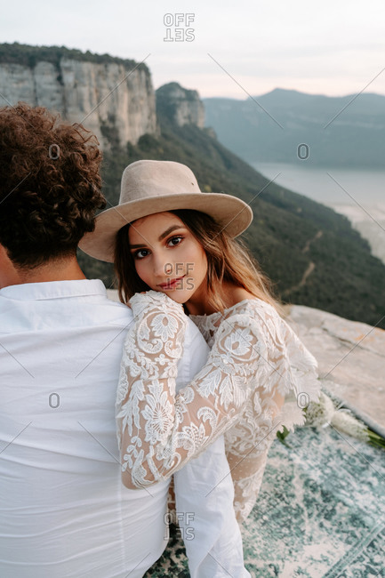 Back view of young unrecognizable man embracing happy wife in stylish wedding dress smiling looking at camera while enjoying romantic moments together against blurred mountainous landscape of Morro de Labella in Spain