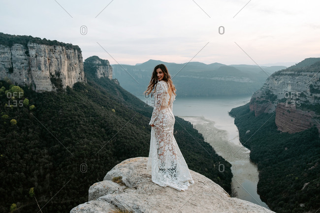 Full length back view of charming young woman in translucent white wedding gown looking at camera while standing on edge of rocky cliff against spectacular scenery with mountains and lake of Morro de Labella in Spain