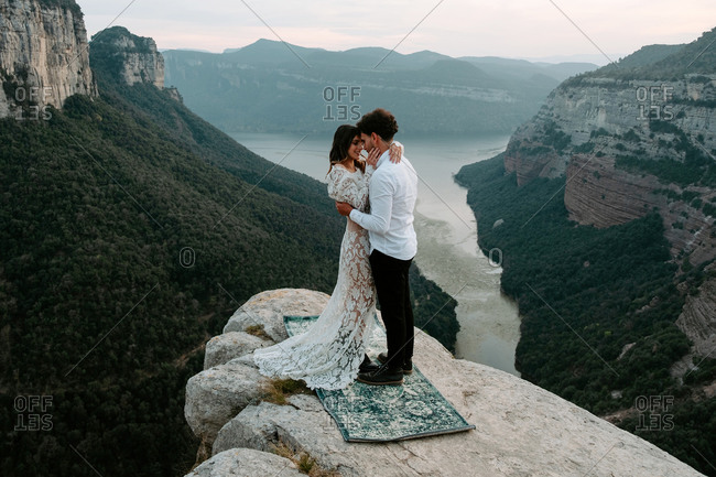 Side view of newlywed young man and woman in elegant clothes standing on top of rocky cliff of Morro de Labella embracing each other and kissing gently