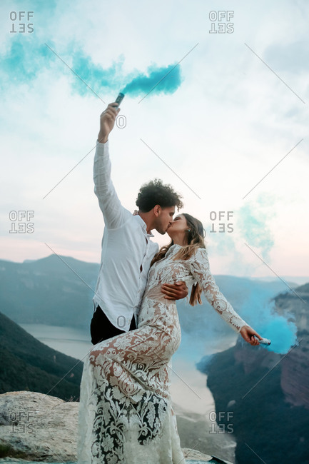 Full body side view of happy young newly married couple in elegant outfits holding colorful smoke bombs and kissing while celebrating marriage on top of rock in Morro de labella in Spain