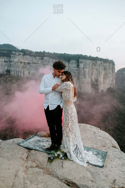 Full body of gentle young couple n stylish wedding outfits standing together with eyes closed on old carpet placed on top of rock with red smoke bomb against amazing scenery of Morro de Labella in Spain
