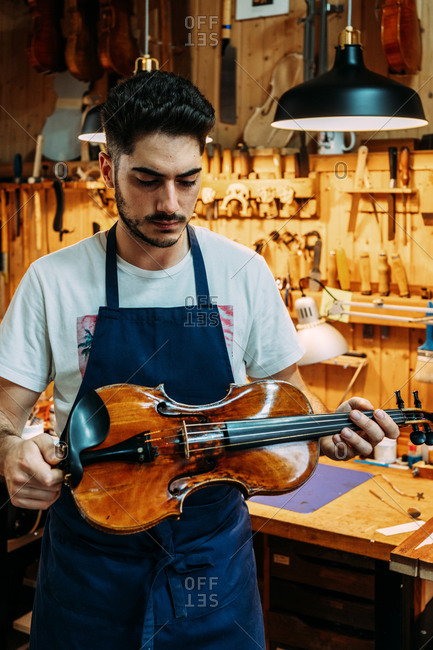 Young craftsman in apron standing with shiny violin near workbench in modern workshop
