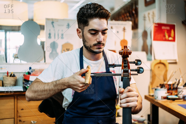 Young professional male artist using peg hole reamer while repairing and tuning string instrument in workshop