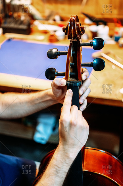 Closeup of violin peg box in hands of anonymous luthier during process of repairing and tuning instrument in workshop