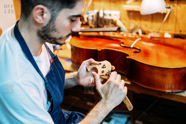 Side view of skilled young male artisan with knife carving wooden violin bridge while creating string instrument in workshop