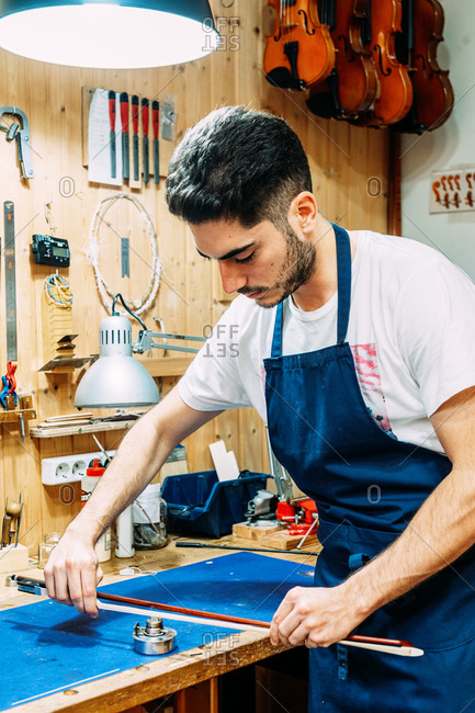 Young artisan luthier standing at workbench and repairing violin bow while working in professional workshop