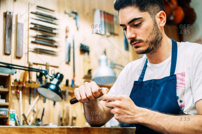 Serious young artisan luthier processing hair for violin bow with professional tool while working in workshop