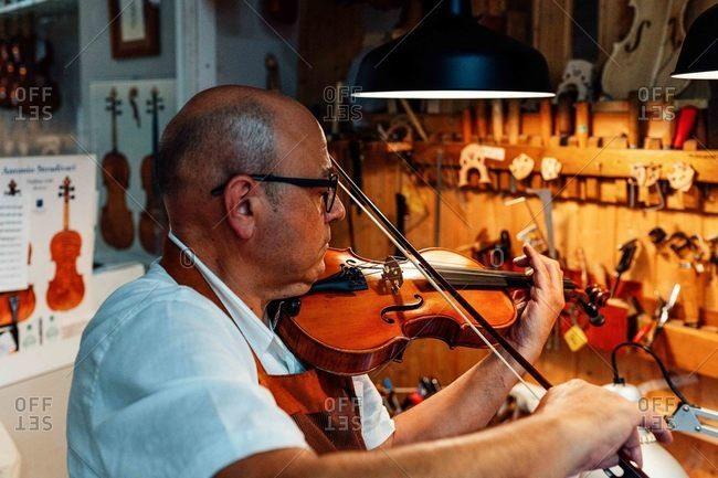 Side view of mature male artisan luthier testing violin after restoration in workshop