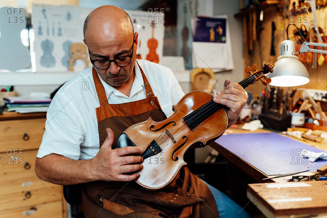 Mature male luthier in apron and glasses sitting on chair and holding restored violin while working in workshop