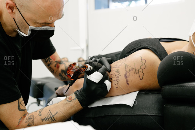 Crop male tattooist with machine making tattoo on arm of woman lying on table with closed eyes in salon