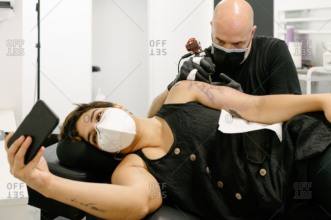 Content female in protective respirator lying on table and taking photo on smartphone while getting tattoo in salon with male artist
