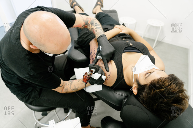 Tattooist with machine making tattoo on arm of woman lying on table in salon