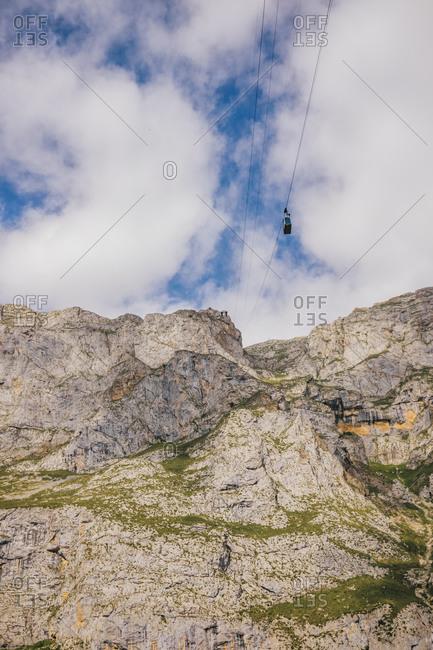 From below of Picos de Europa mountain range under blue cloudy sky in Asturias
