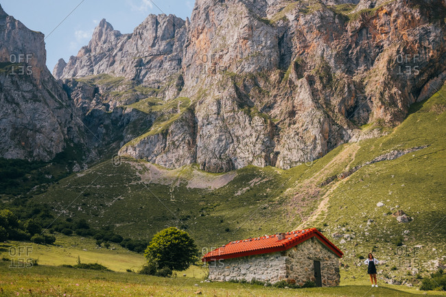 Woman standing in majestic landscape of Picos de Europa mountain range near small stone cabin located on green meadow on sunny day in Asturias