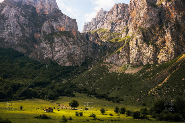 Majestic landscape of Picos de Europa mountain range and small stone cabin located on green meadow on sunny day in Asturias