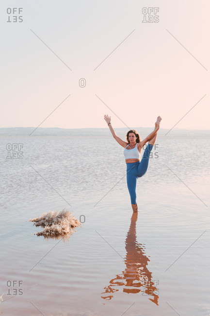Full body of female in sportswear standing in lake water and performing standing split asana with arm raised while practicing yoga in sunny evening