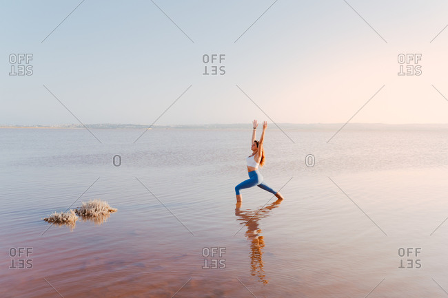Full body side view of unrecognizable focused female in sportswear standing in water and performing warrior one pose during hatha yoga practice at lake in summer evening