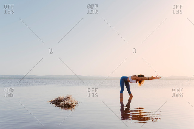Full body side view of unrecognizable focused female in sportswear standing in water and performing Half Forward Bend during hatha yoga practice at lake in summer evening