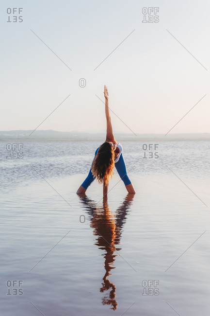 Full body of unrecognizable flexible female in sportswear doing Revolved Wide Legged Forward Bend while standing in calm lake water and practicing yoga in summer evening