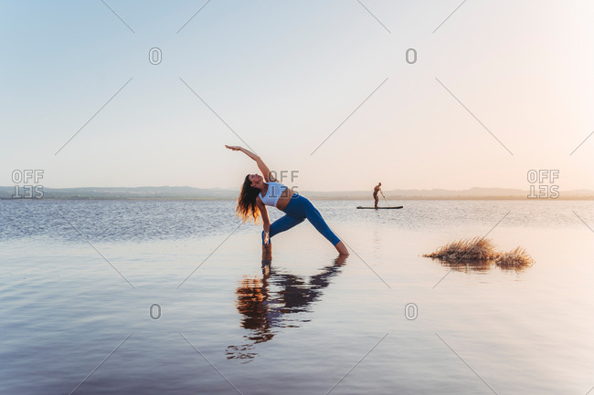 Full body of unrecognizable slim female in sportswear stretching in Extended Side Angle yoga asana during practice on lake shore against cloudless sunset sky with distant man surfing on paddle board in background