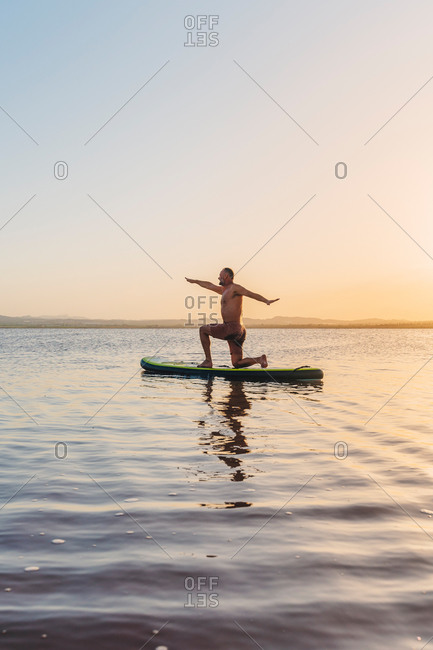 Full body side view of unrecognizable man doing variation of Crescent Lunge on Knee asana while floating on paddle board in calm lake water during sunset