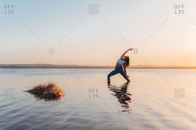 Full length of young slim female in activewear standing in Reverse Warrior pose in calm lake water during summer sunset